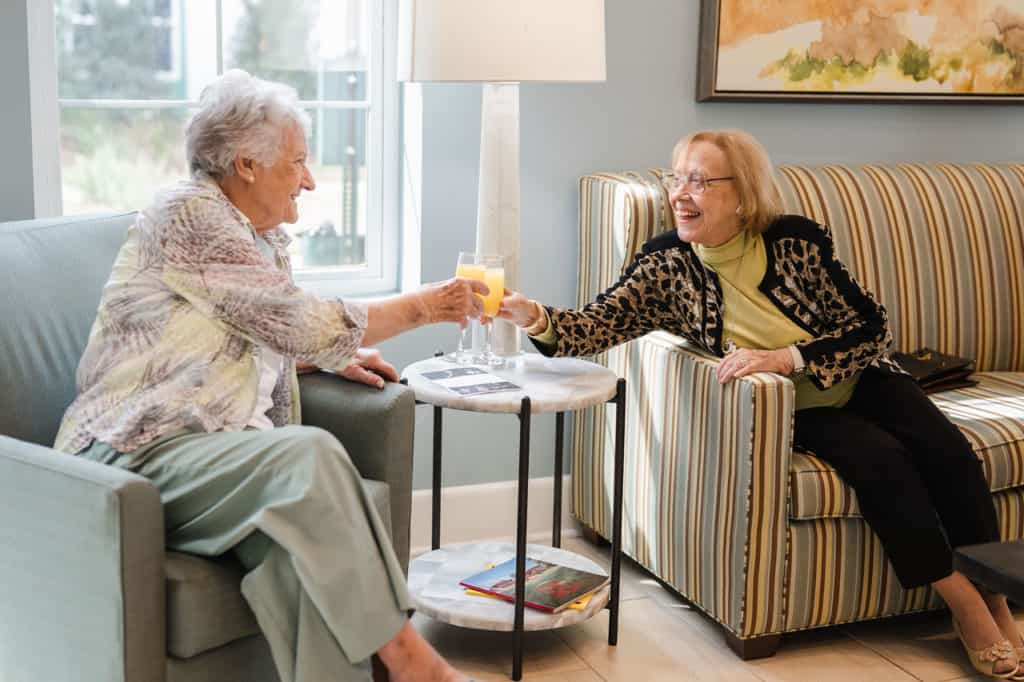 Two senior women seated toasting champagne
