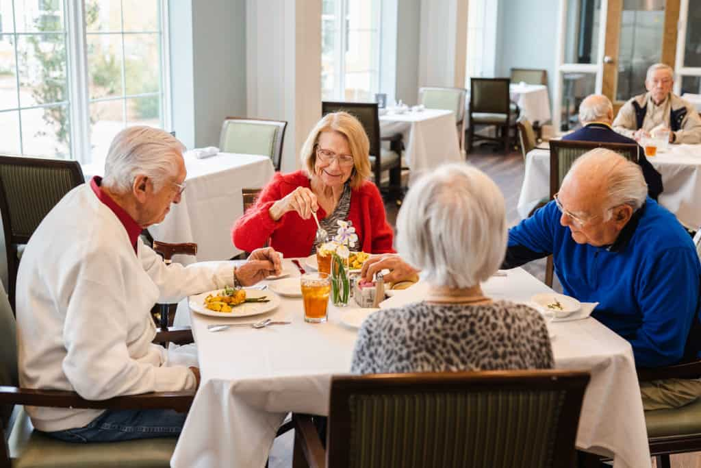 Seniors seated at dining table eating
