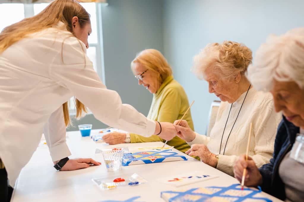 Staff assisting senior women painting