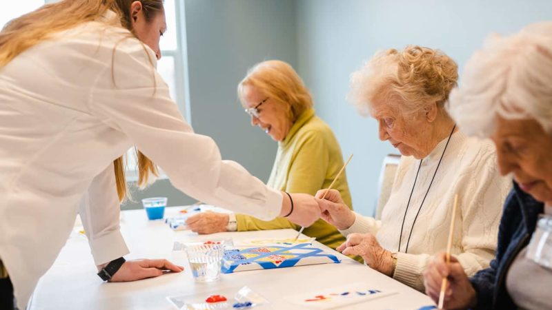 Staff assisting senior women painting