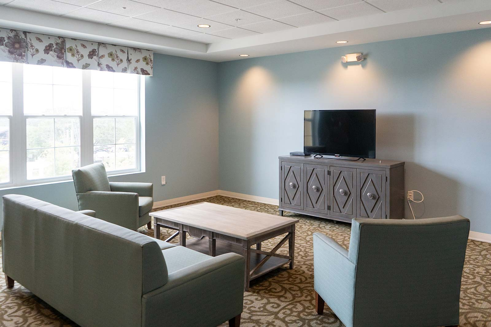 Gathering area with TV, couches and chairs at The Arbors of Gulf Breeze an Independent Living, Assisted Living and Memory Care community in Gulf Breeze, FL